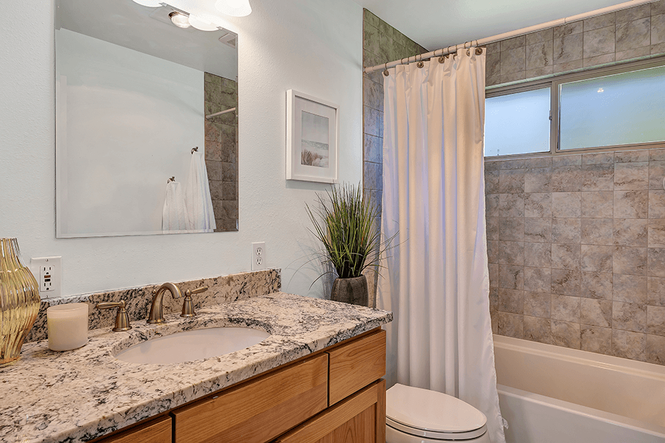This tastefully appointed full bath on the main features a granite countertop and tile bath surround.