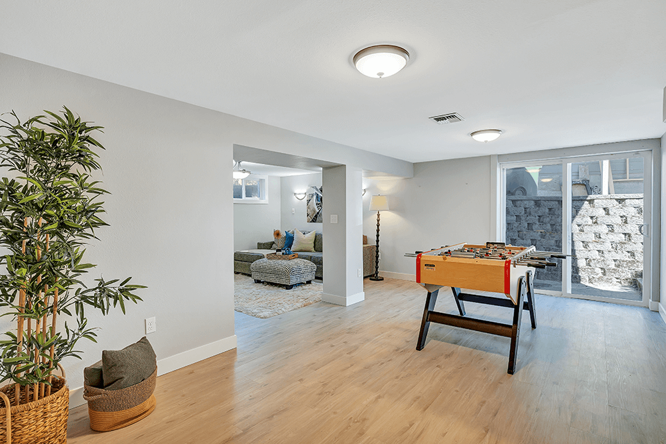 The family room opens to extra space perfect for a pool table, ping pong table or foosball table. There is also exterior access to the side of the home through the sliders.