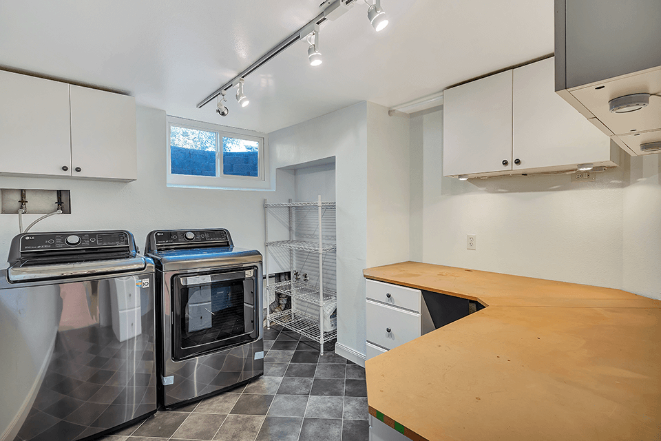 The utility room features a fabulous washer and dryer that stay with the home as well as a craft area with a large work surface and plenty of cabinets and drawers.