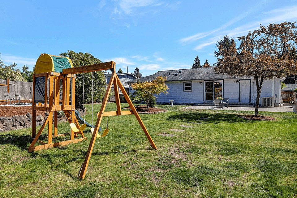 The backyard features an expansive patio, a play structure, a firepit area, a raised bed garden and blueberry bushes that produce copious blueberries in the summer!
