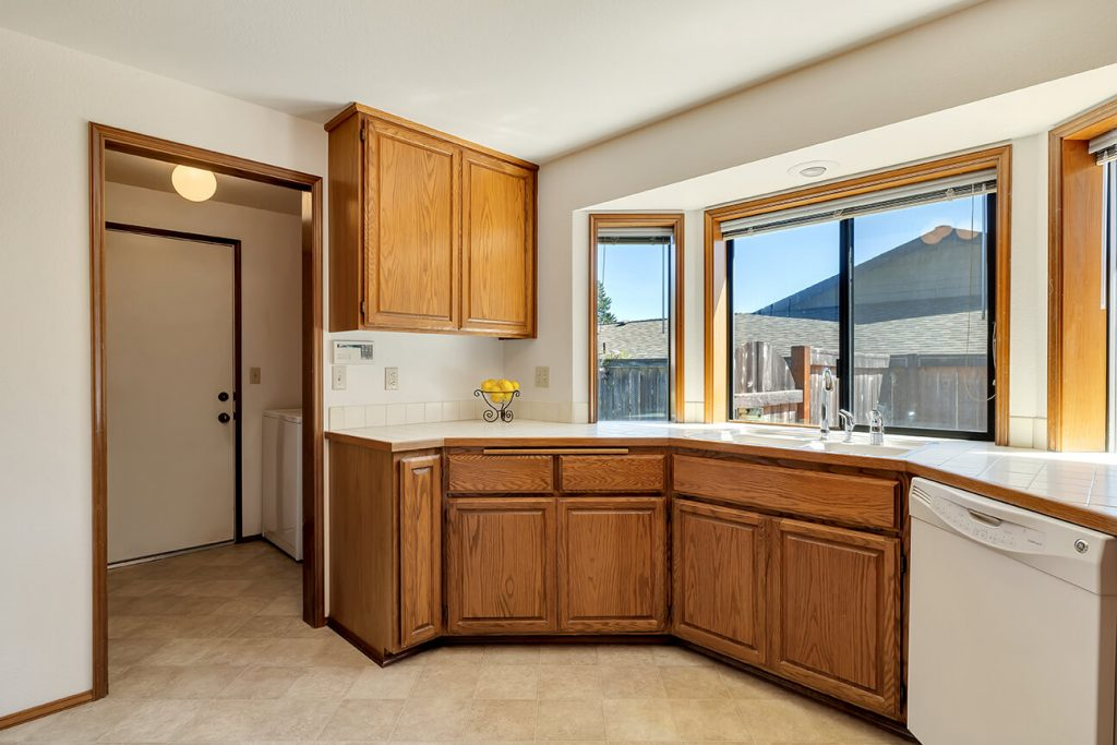 The kitchen boasts large picture windows, plenty of counterspace and cabinet space and matching all-white appliances.