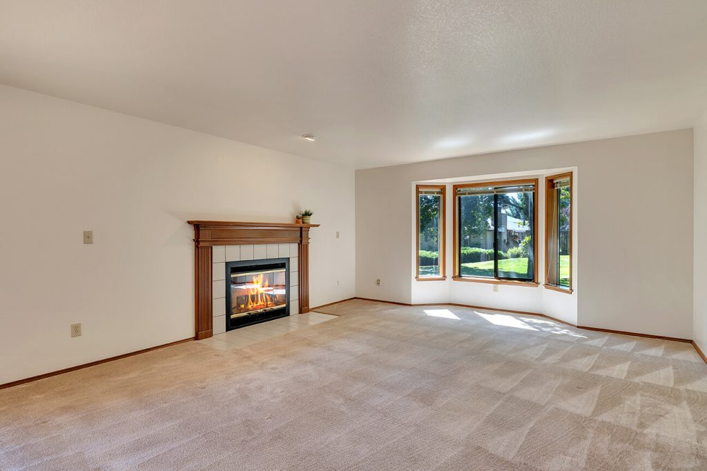 The living room features a wood-burning fireplace and a huge bay window that frames the gorgeous green belt outside.