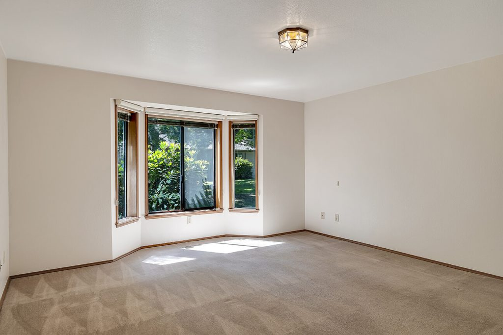 The spacious master bedroom features a large bay window framing the lush greenery.
