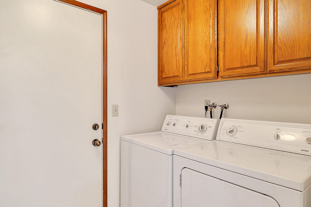 Just off the kitchen is the utility room with extra storage and a large pantry (not shown). The washer and dryer stay.
