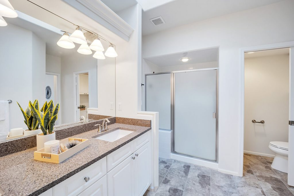 The beautifully remodeled ensuite bath boasts granite countertops, dual sinks, a walk-in shower and a separate WC.