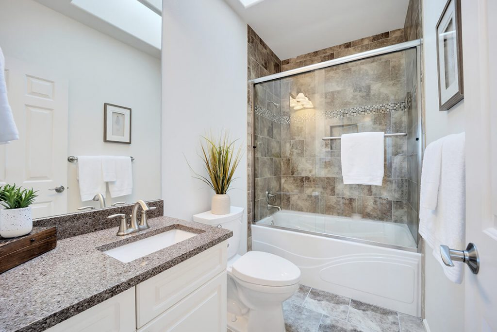 And this is the remodeled guest bathroom with granite countertops, new hardware, a tile shower surround and a soaking tub. Simply elegant!