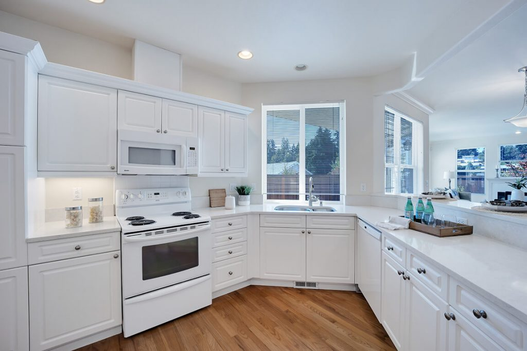 This updated kitchen features lovely quartz countertops, newer white-on-white appliances and extensive cabinetry.