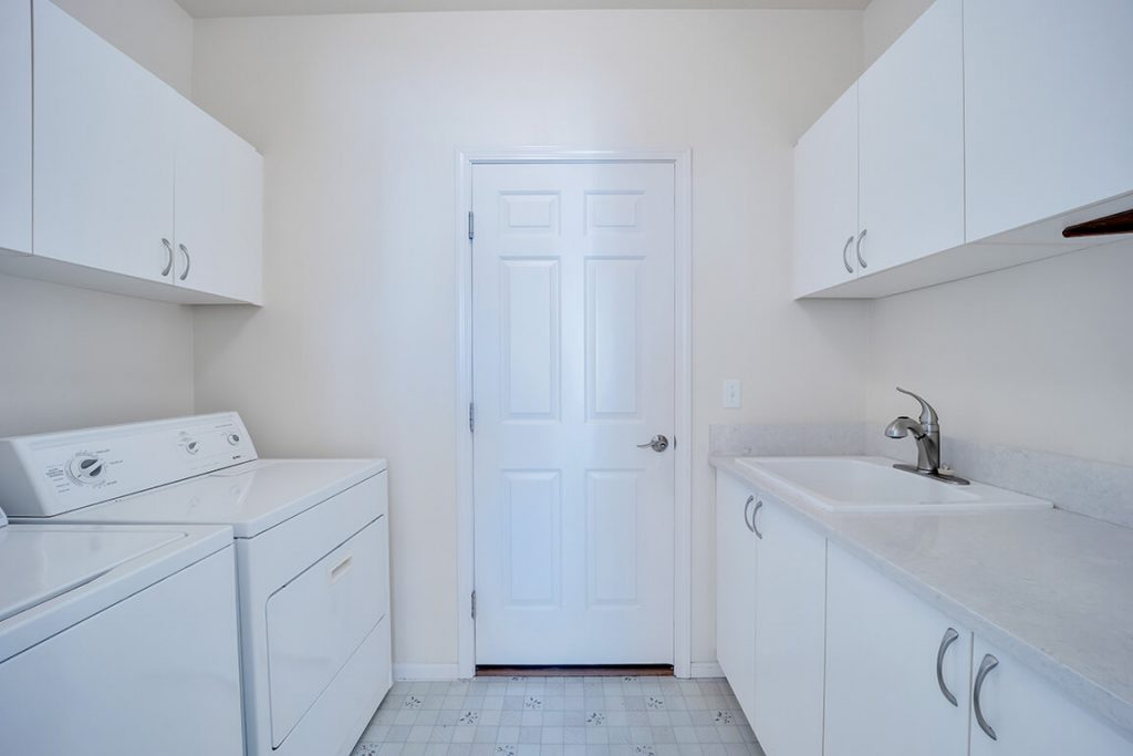 The utility room offers extra cabinet space, a utility sink and the washer and dryer stay with the home.