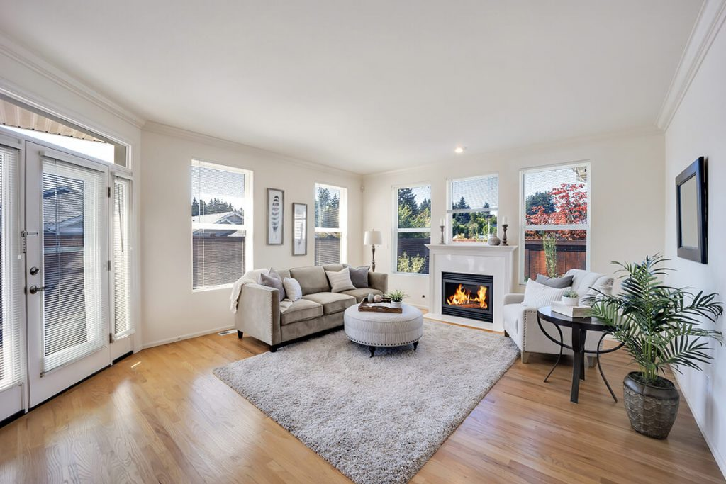 The living room features large picture windows and a cozy gas fireplace.